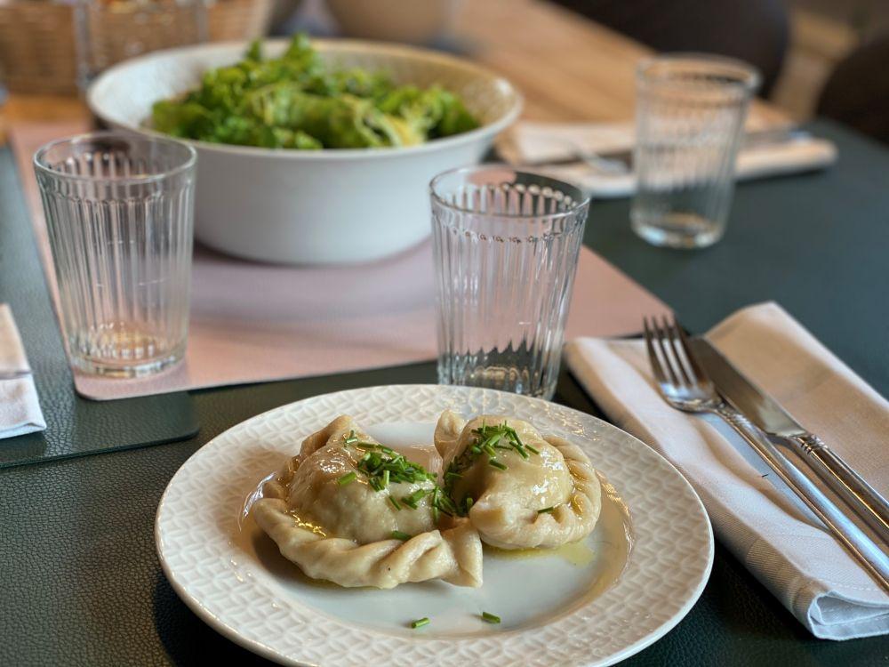 Kärntner Kasnudeln auf einem Teller, im Hintergrund eine Schüssel mit Salat.