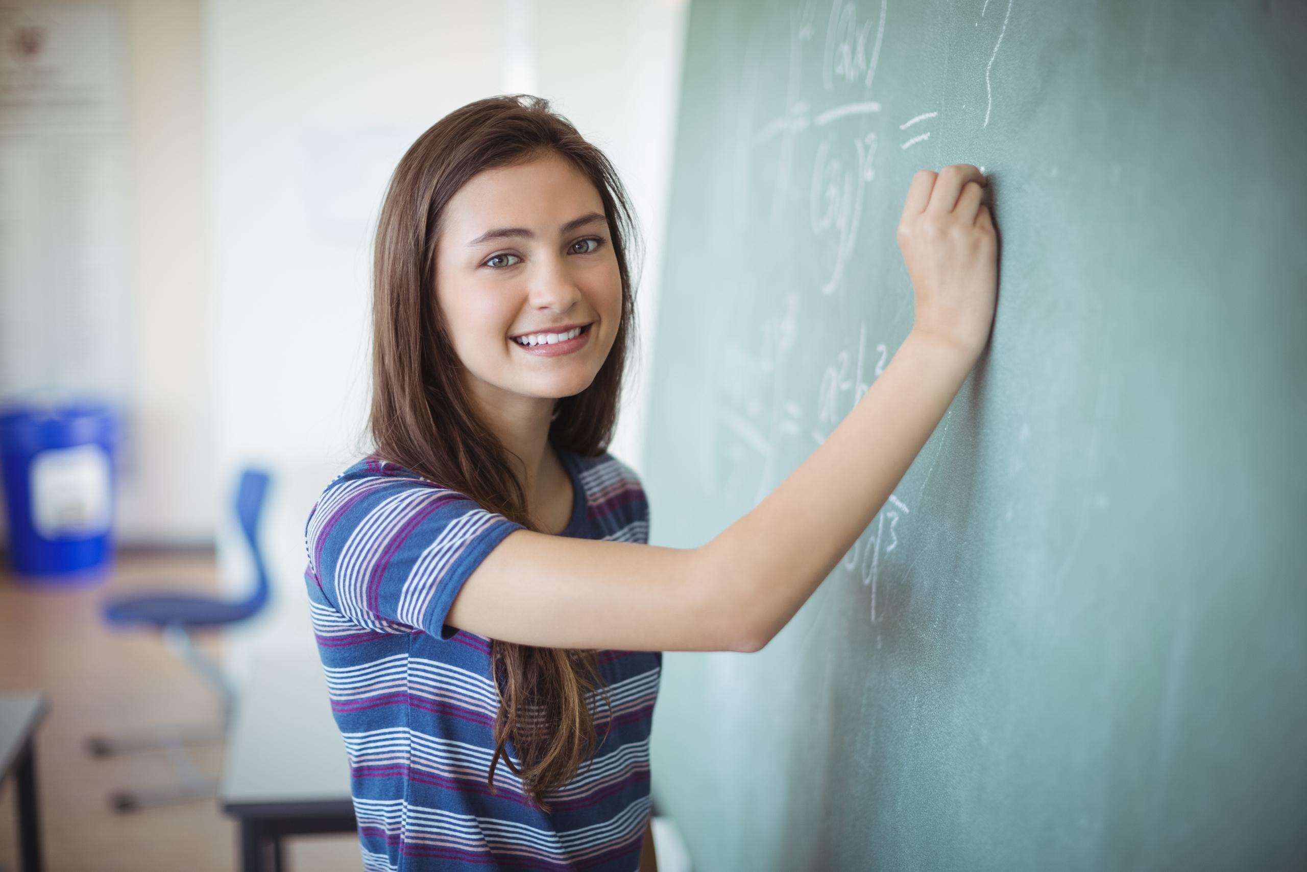 Schoolgirl pretending to be a teacher in classroom | Mathematik_Schülerin an der Tafel
