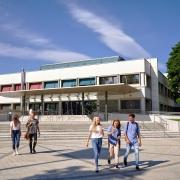 Studierende vor dem Haupteingang der Universität Klagenfurt